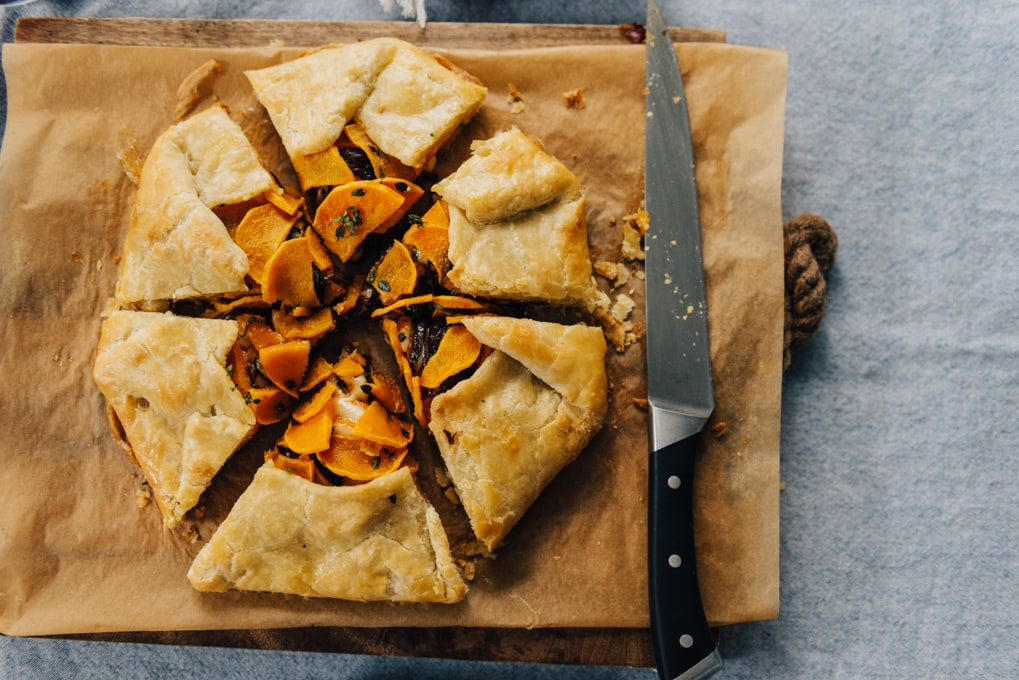 A butternut squash galette sliced into six pieces on a wood cutting board.