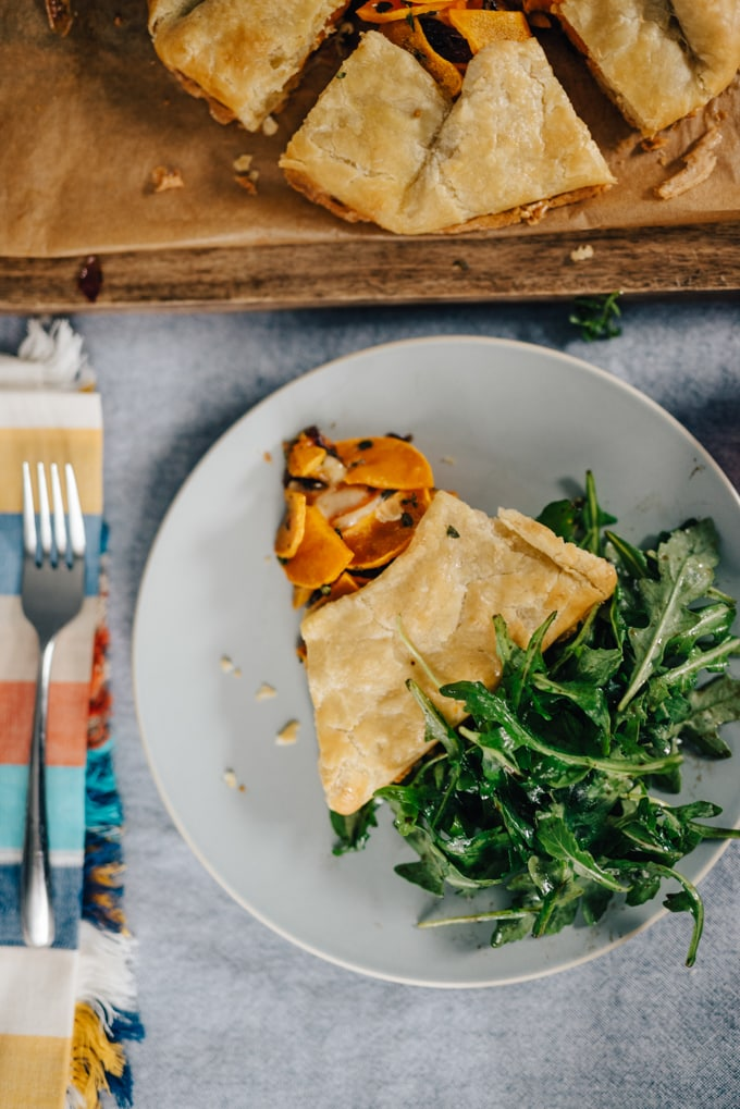 A slice of butternut squash galette with an arugula salad on a blue plate.