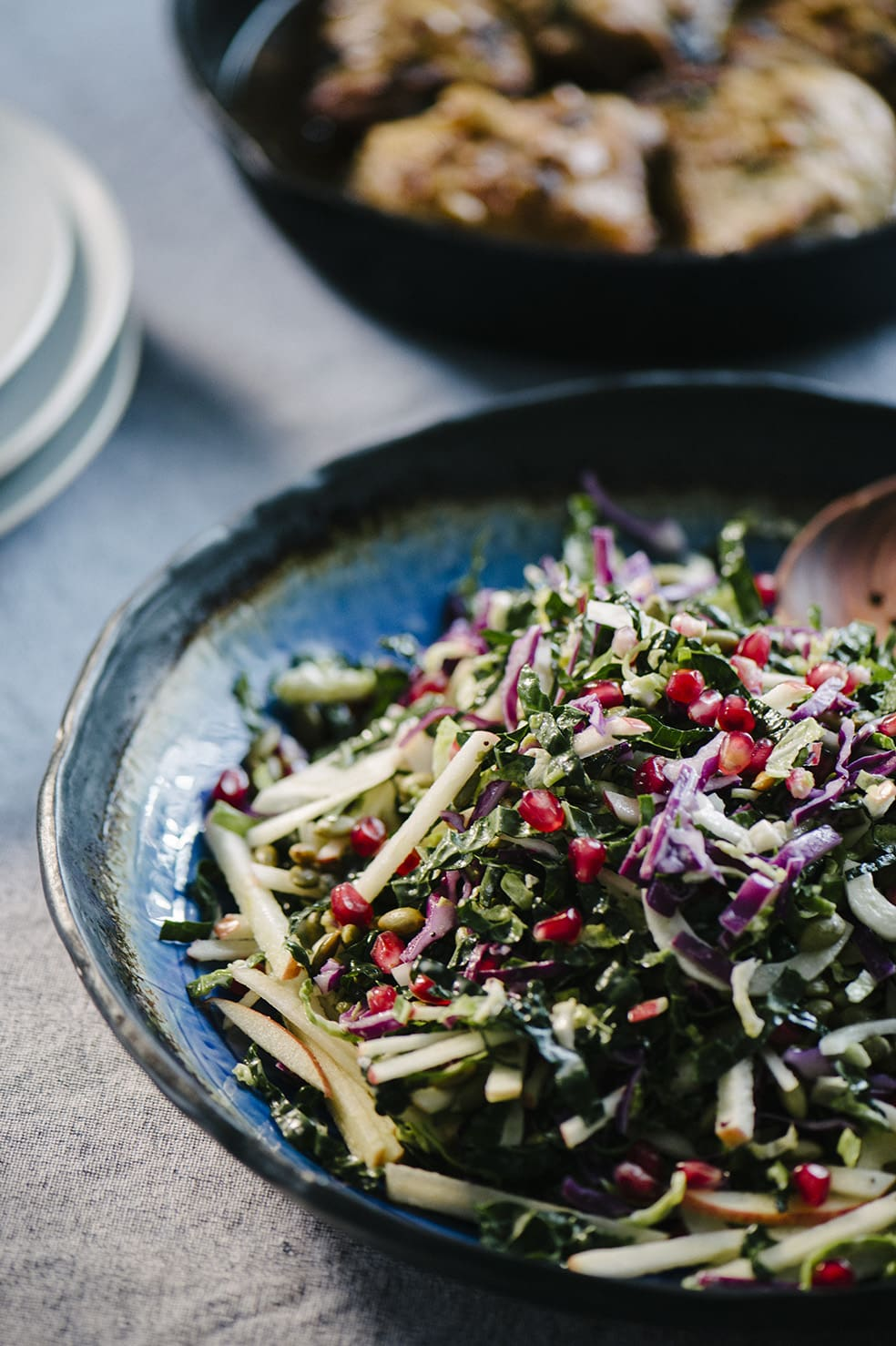 Kale pomegranate salad with apples, fennel, and pepitas in a blue serving dish next to a dish of cast iron skillet roasted chicken.