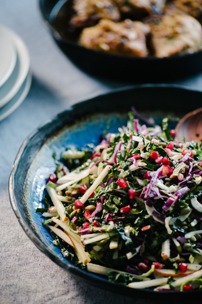 This kale pomegranate salad is a bright, hearty and deeply nutritious cool weather recipe! It's sweet, crunchy, and full of gorgeous color. Ready in just about 30 minutes, this is one of our go-to paleo and whole 30 recipes for fall. #vegetarian #wholefood #realfood #paleo #whole30