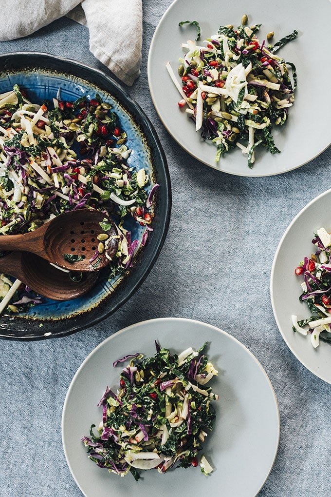A large blue serving bowl of kale pomegranate salad and three plates with servings of salad on a blue tablecloth.