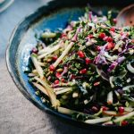 A kale pomegranate salad with apples, fennel, and pepitas in a blue ceramic bowl.