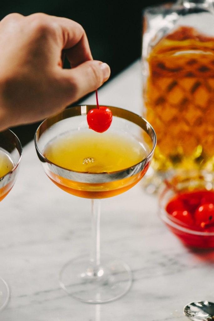 A woman's hand placing a maraschino cherry garnish into a cherry manhattan cocktail.