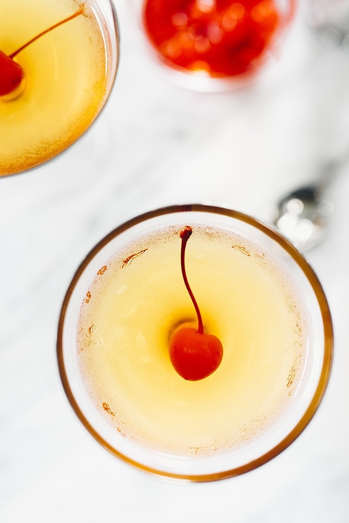 An overhead view of cocktail glass filled with a black cherry manhattan and garnished with a cocktail cherry.