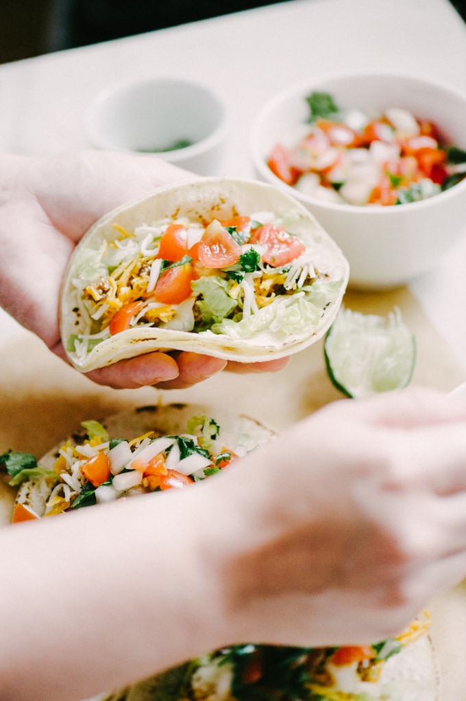 A woman's hands holding a ground beef tac, spooning homemade pico de gallo on top.