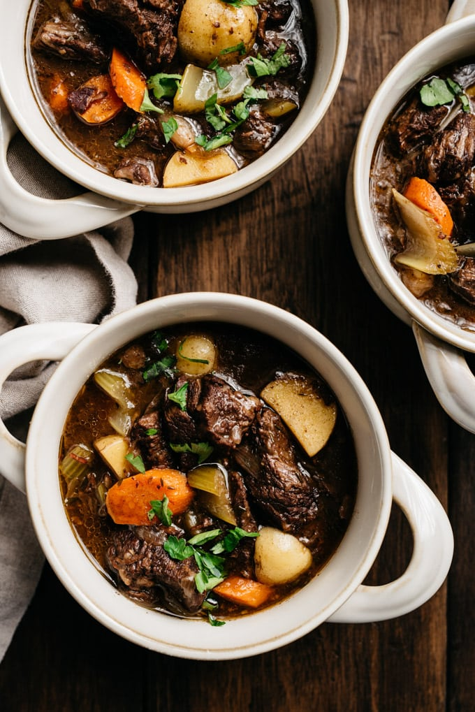 Three bowls of dutch oven braised red wine beef stew with potatoes, carrots, and celery on a wood table with a linen napkin.