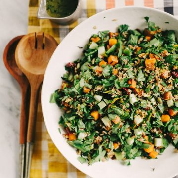 A bowl of roasted sweet potato salad with autumn greens, apples, seeds, and vegan maple vinaigrette.