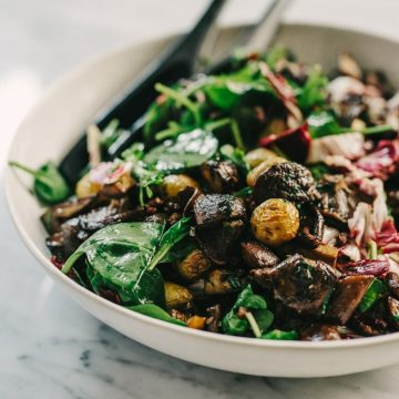 This warm mushroom salad with potato and wilted greens is one of my favorite fall salads. Crispy, pan-seared mushrooms are the star, tossed with roasted potatoes and fall greens for a hearty and satisfying meal. #paleo #wholefood #realfood #fall #autumn