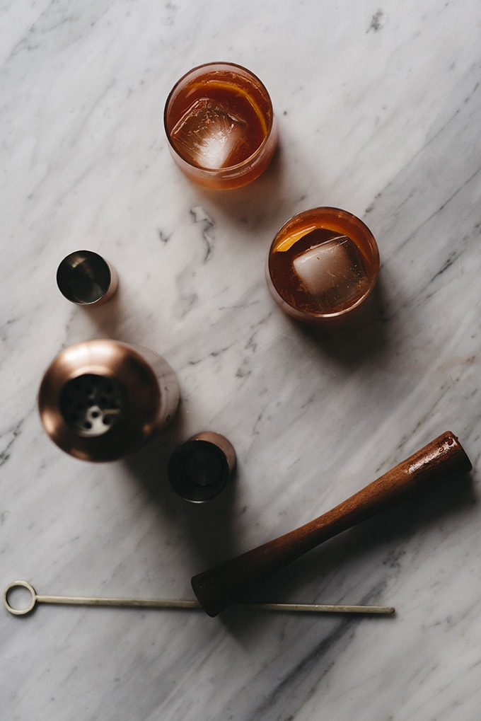 Two old fashioned cocktails on a marble table with a bronze cocktail shaker and wood muddler.