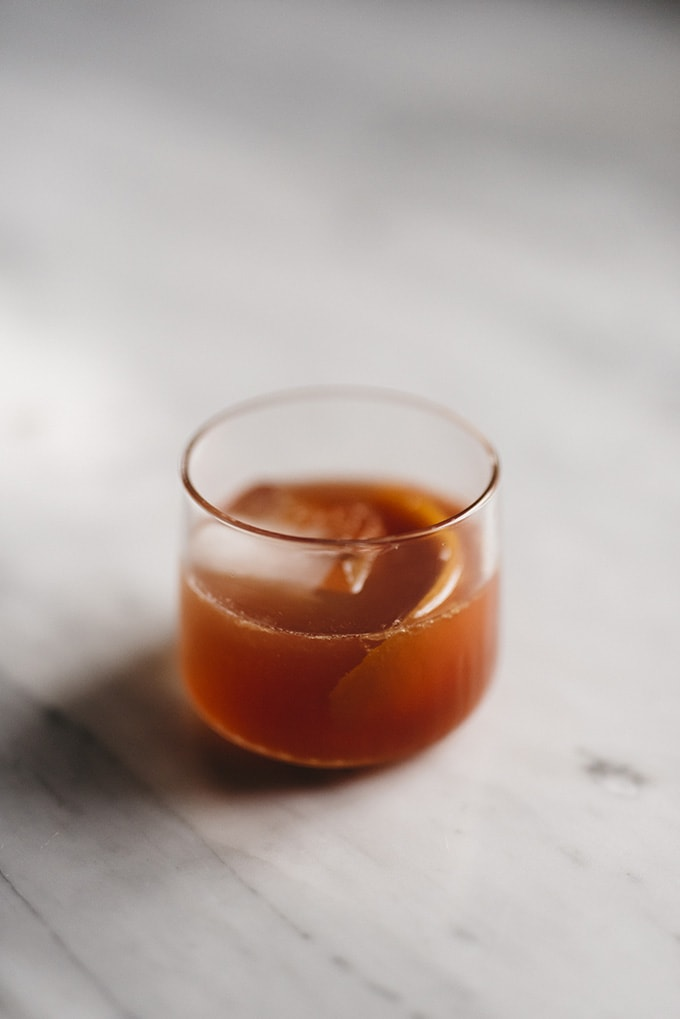 An old fashioned cocktail with a giant ice cube and orange peel garnish on a marble table.