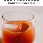 A classic old fashioned bourbon cocktail in a cocktail glass with a giant ice cube and orange peel garnish.