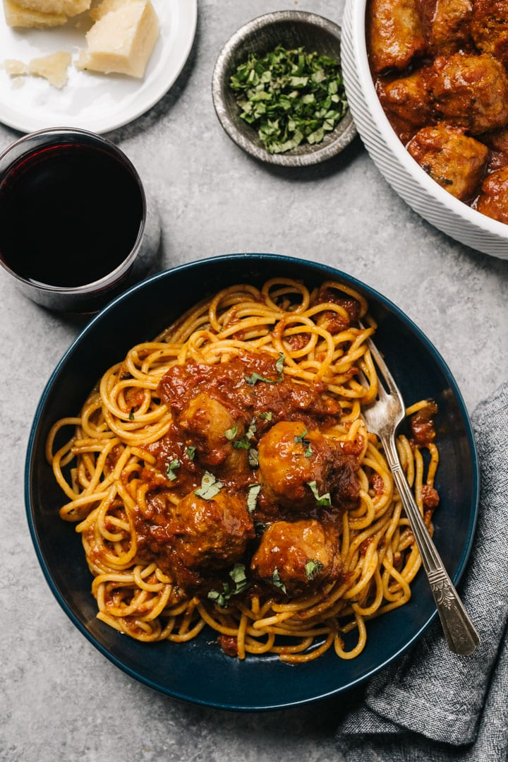 Spaghetti tossed with sunday sauce and topped with meatballs in a blue pasta bowl on a cement table with a glass of red wine, small bowl of chopped basil, and wedge of parmesan cheese.