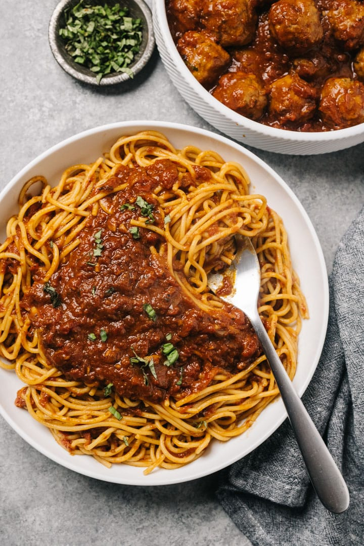 A large serving bowl of spaghetti tossed with sunday sauce with meatballs and sausages in a serving bowl on the side.