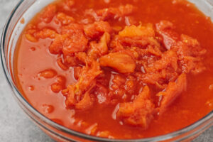 Hand crushed whole canned tomatoes in a glass bowl.