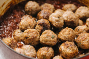 Homemade meatballs added to sunday sauce in a red dutch oven.
