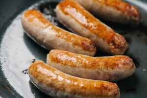 Italian sausage links browning in a skillet.