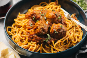 Side view, homemade meatballs and sausages in sunday gravy sauce over spaghetti in a blue pasta bowl.