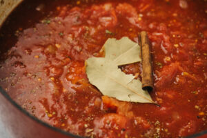 Sunday sauce in a dutch oven topped with bay leaves and a cinnamon stick before simmering.