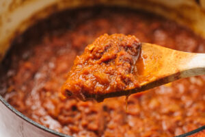 A wood spoon covered in slow simmered sunday sauce hovering over a pot on the stove.