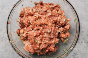 Ground beef and ground pork mixed with eggs and seasoning in a large glass mixing bowl.
