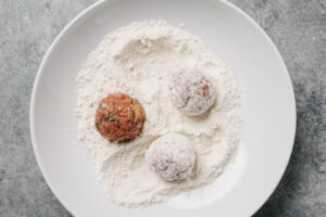 Meatballs dusted with flour in a shallow white bowl.