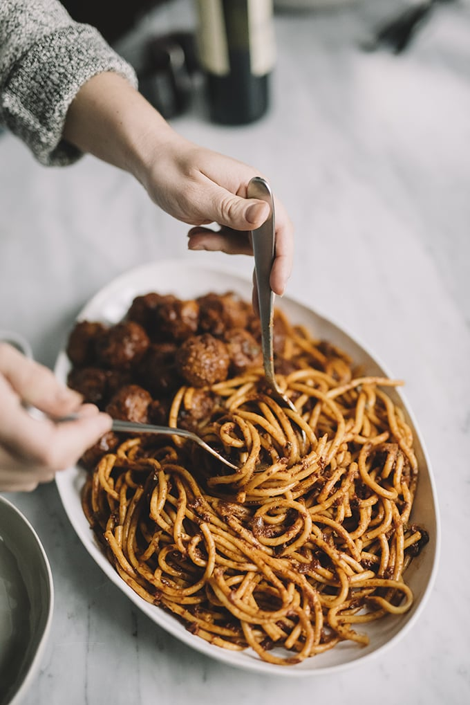 A woman tossing a platter of pasta with homemade sunday sauce.