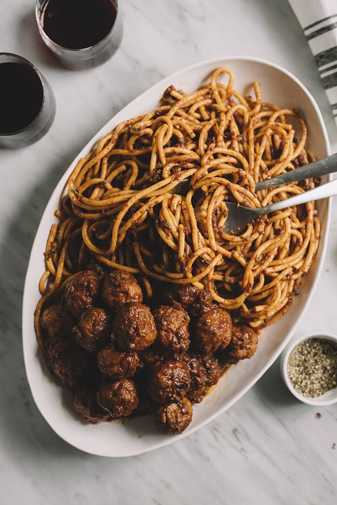 A large serving platter of pasta tossed with homemade sunday sauce and served with homemade meatballs.