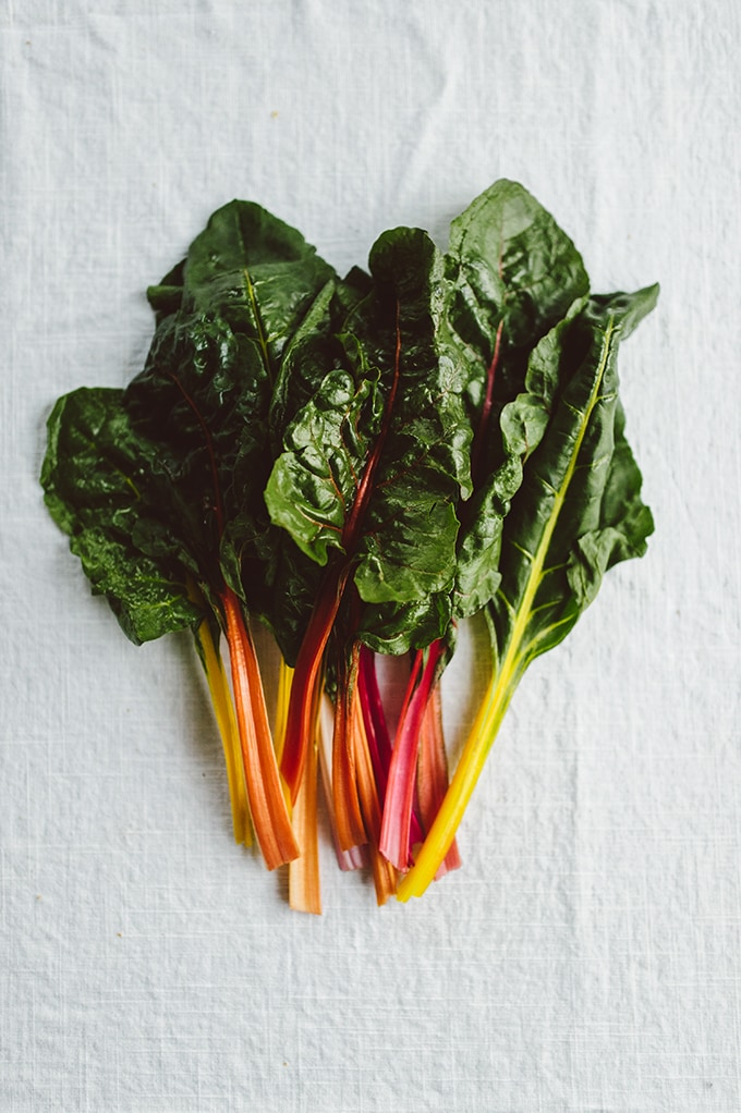 Raw rainbow swiss chard, a key component to green detox soup, on a white linen tablecloth.