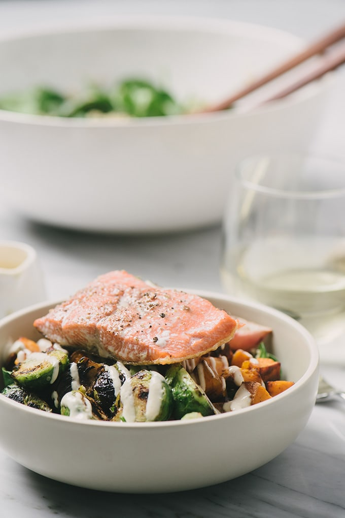 A side view of a salmon quinoa bowl alongside a glass of wine on a marble table.
