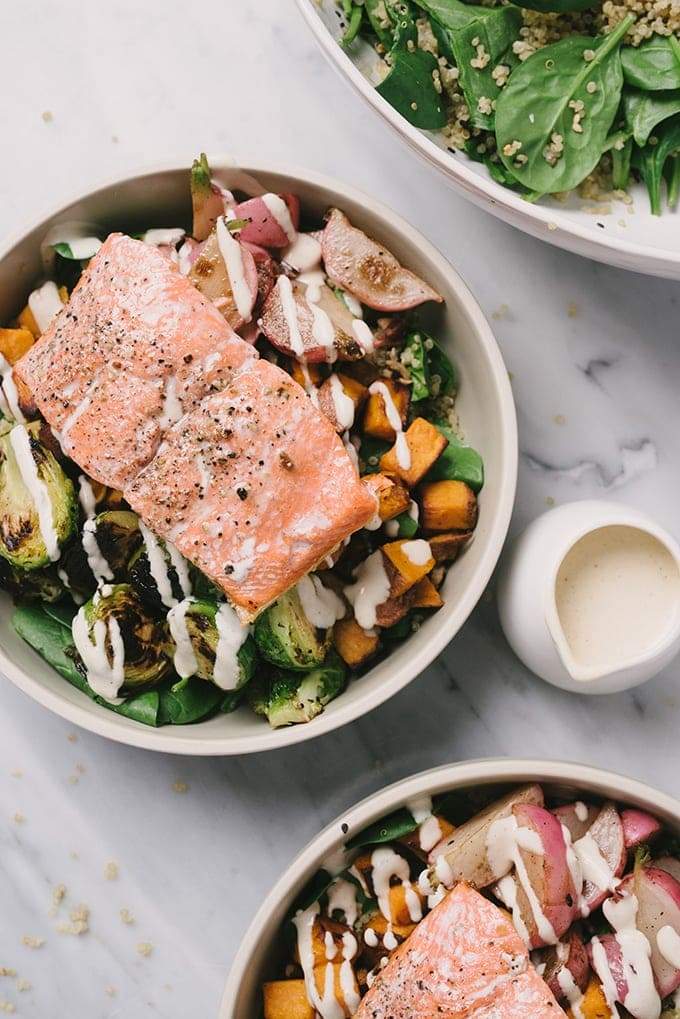 An overhead image of a salmon quinoa bowl made with fresh spinach tossed with quinoa and sesame seeds, reheated leftover vegetables, a pan seared salmon filet, and lemon tahini dressing.