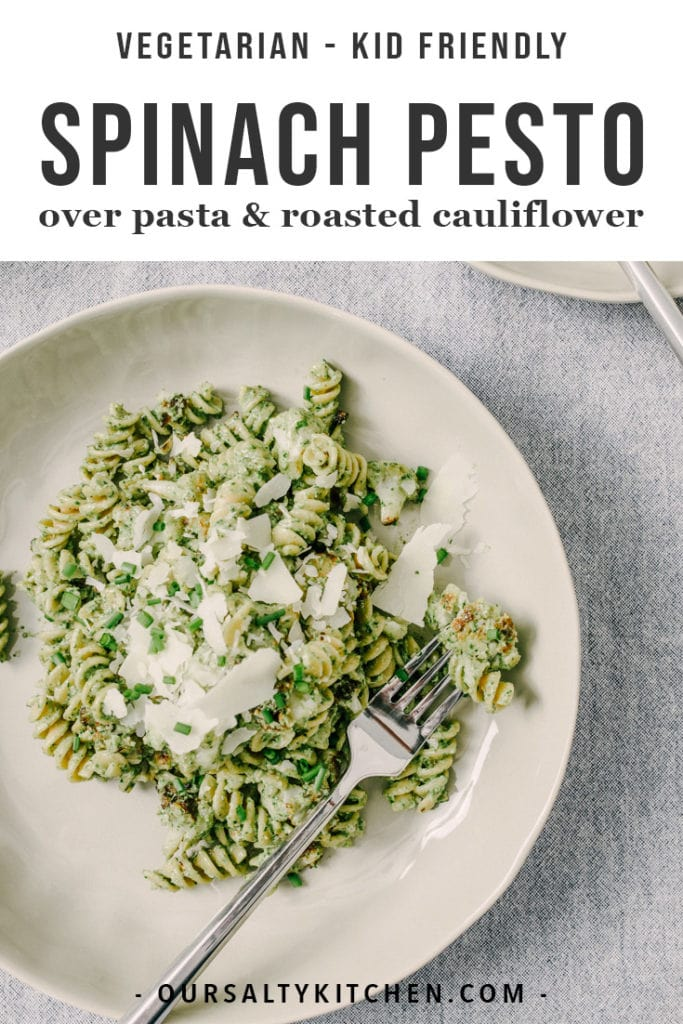 A serving of spinach pesto over whole grain pasta and roasted cauliflower garnished with fresh parmesan cheese.