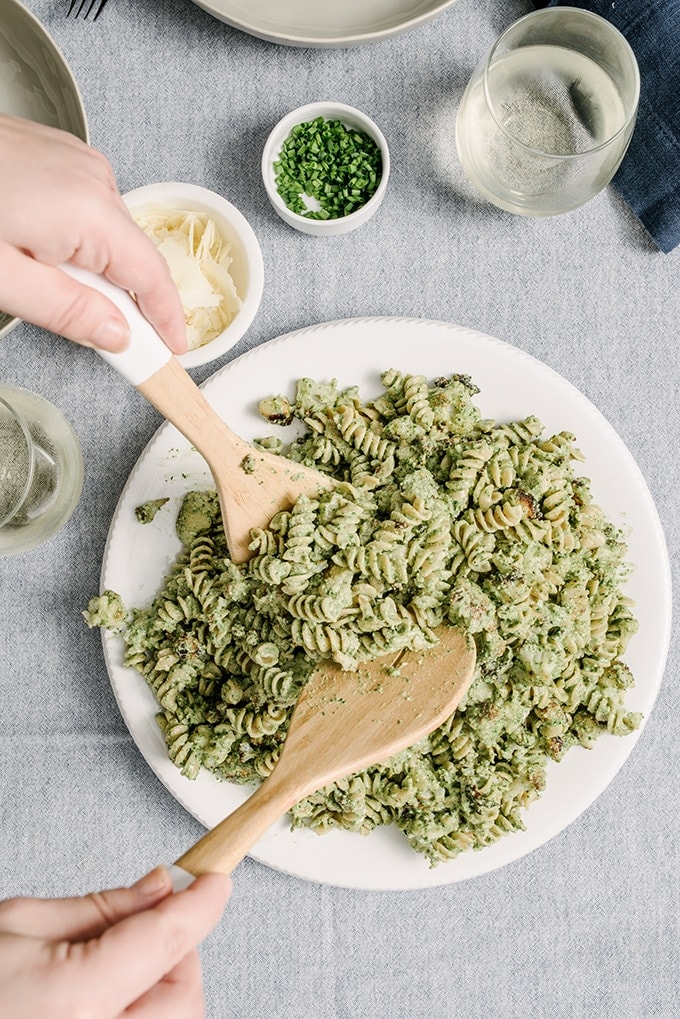 A woman tossing a platter filled with rotini pasta and roasted cauliflower dressed with ricotta spinach pesto.