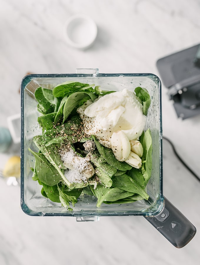 An overhead view of a blender filled with the ingredients for spinach pesto - baby spinach, garlic, ricotta cheese, and seasonings.