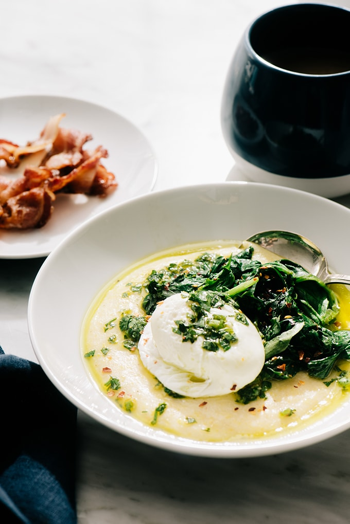 A white bowl filled with breakfast polenta topped with a poached egg and sautéed spinach, with a blue coffee mug and side plate of bacon.