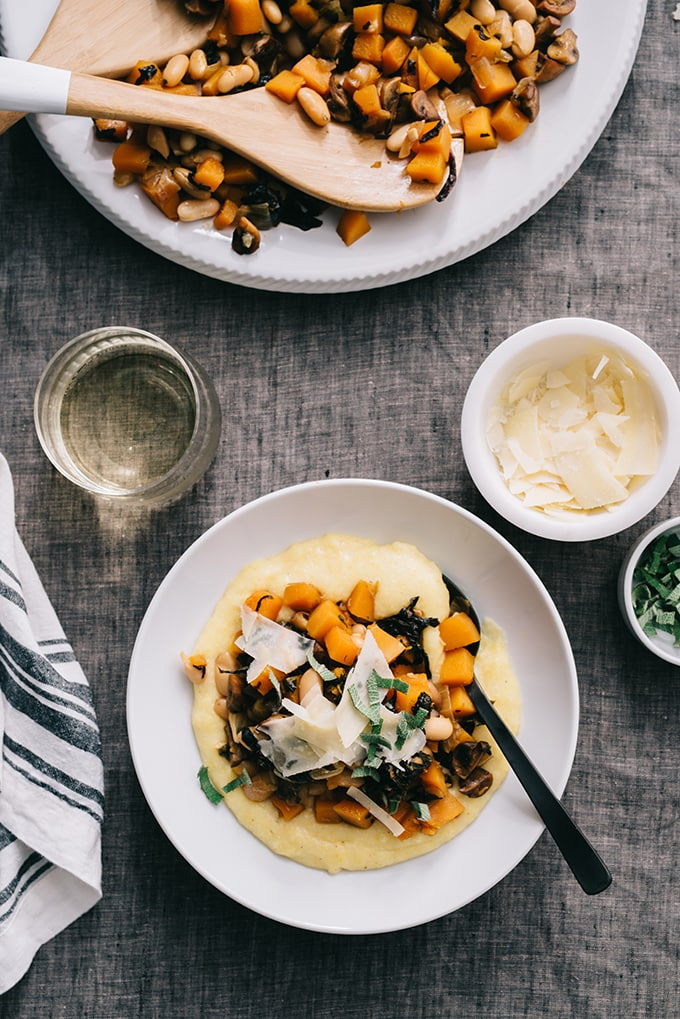 An individual bowl of white bean ragout over polenta alongside a large serving dish filled with white bean ragout and small side dishes filled with shaved parmesan cheese and fresh sage.