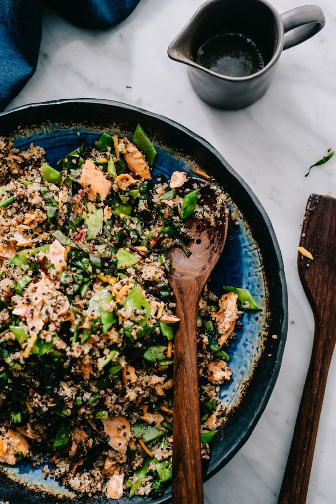 Salmon quinoa salad in a serving with with a side of honey soy dressing in a small pitcher on the side.