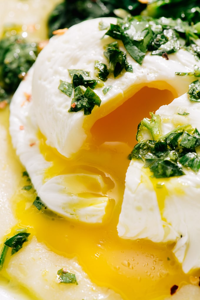A detail image of a poached egg with a runny yolk over gluten free breakfast polenta.
