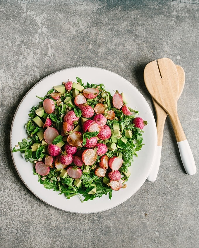 A large platter of roasted radish salad with greens, farro, avocado and a mint Italian salsa verde dressing.