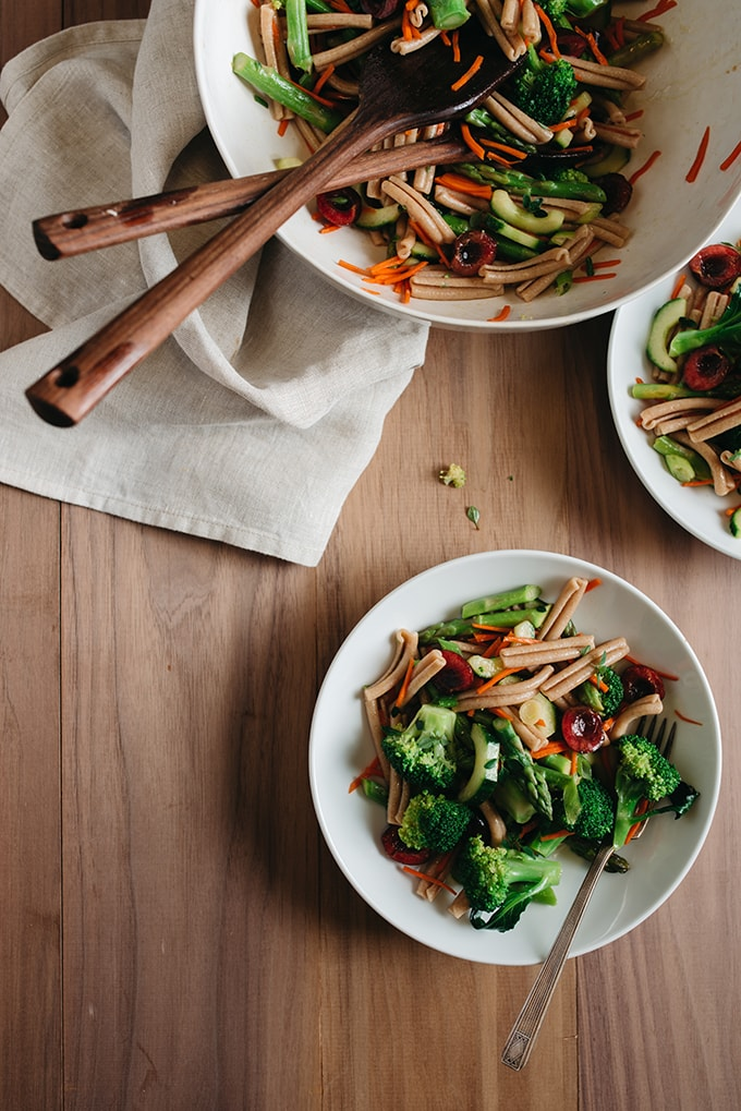 An overhead view of a serving bowl and two small side dishes filled with healthy broccoli pasta salad on a wood table.