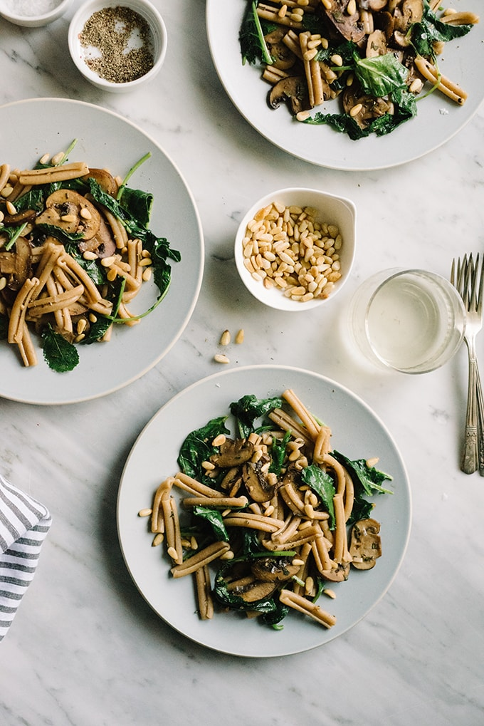 Three plates of kale pasta with mushrooms and pine nuts on a marble table with glasses of white wine.