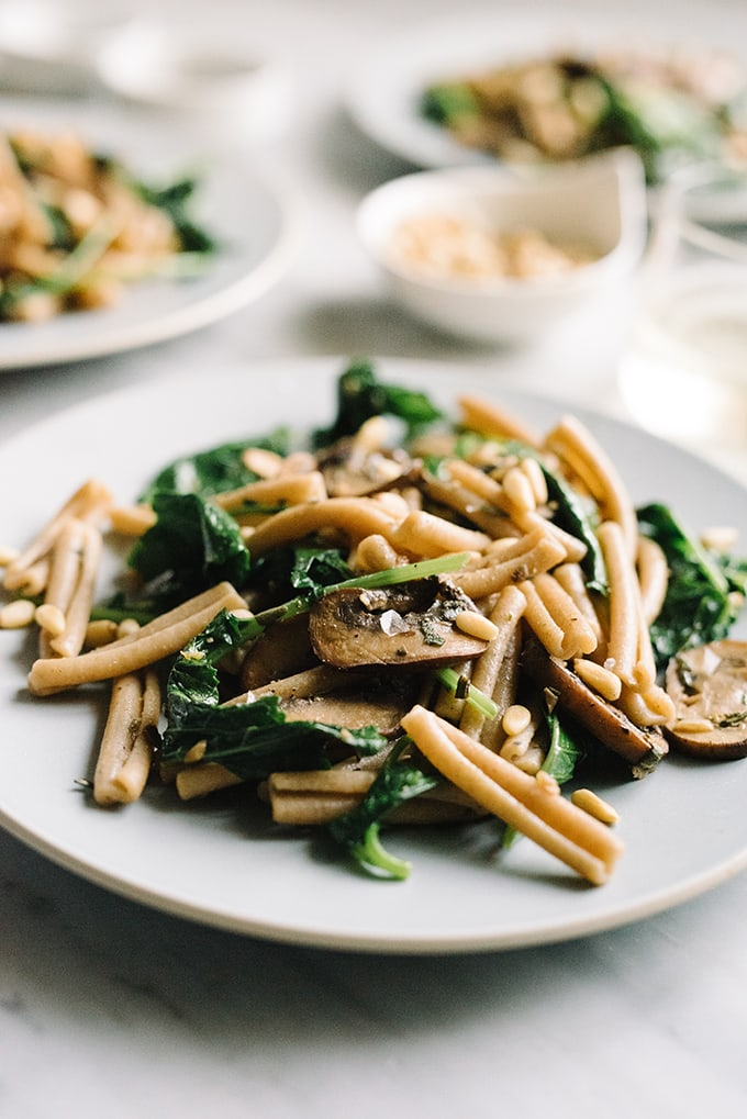 Side view, mushroom and kale pasta with white wine pan sauce on a blue plate.