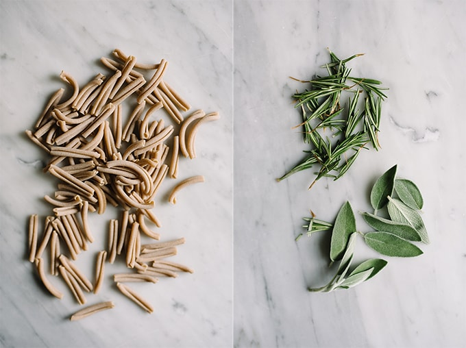 Left - raw whole wheat gemelli pasta noodles on a marble table. Right, fresh rosemary and sage leaves on a marble background.