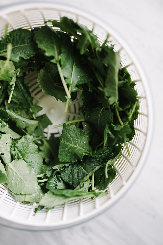 Baby kale in a salad spinner on a marble counter.
