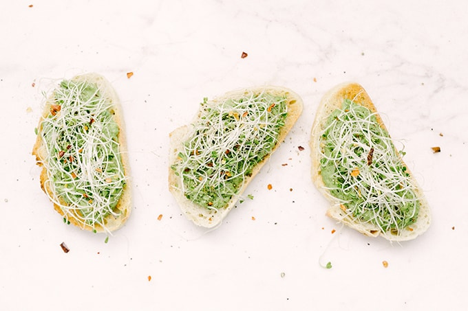 This roasted garlic sweet pea bruschetta is a sweet, seasonal spring recipe. It's great as an appetizer for a dinner party or served with a bit of extra protein and veggies for an open-faced sandwich.