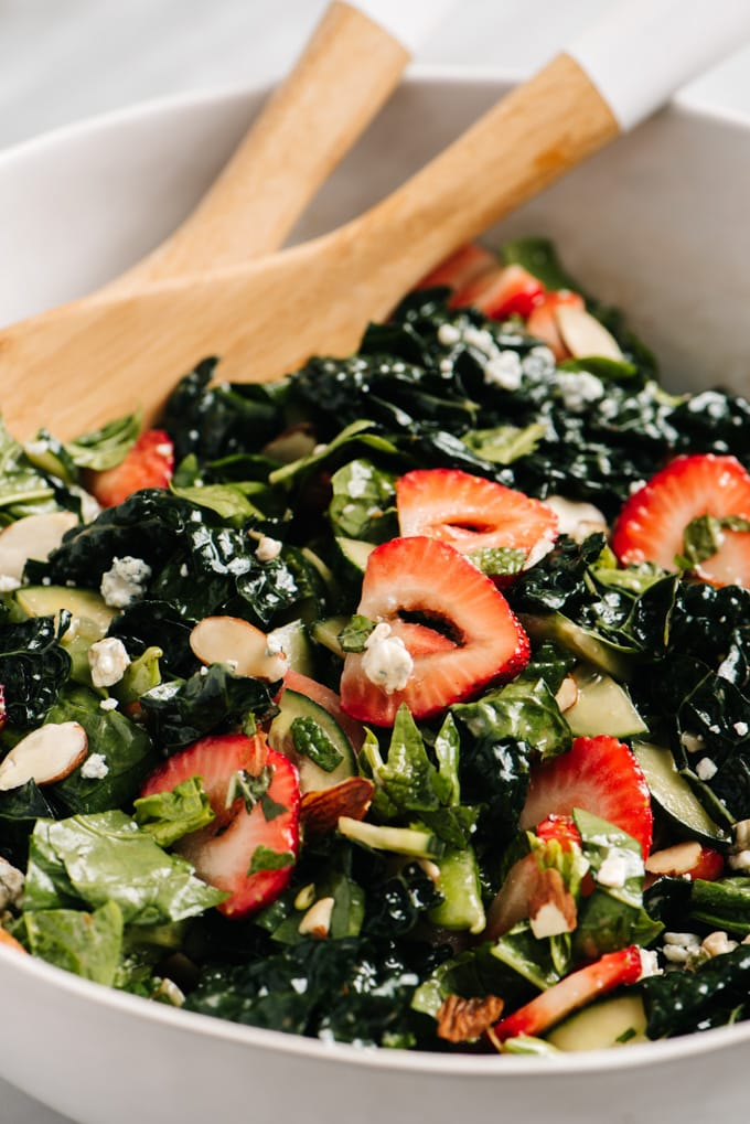 Strawberry kale salad with balsamic vinaigrette in white serving bowl with wood serving spoons.