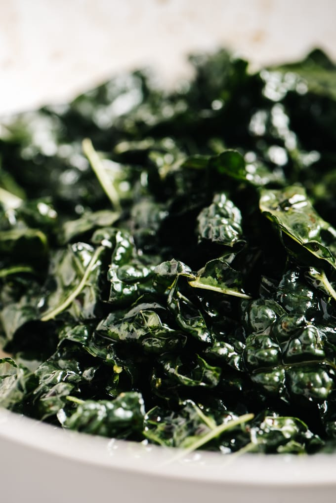 A bowl of chopped kale massaged with balsamic vinaigrette.