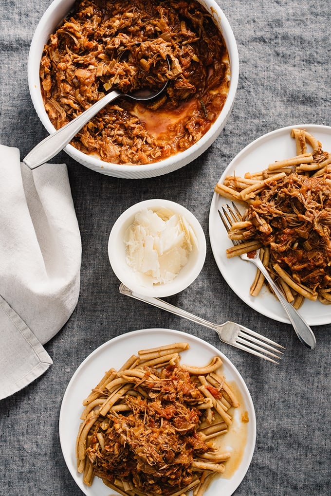 Two servings of pulled pork ragu and one large serving dish of pork ragu on a table with a grey tablecloth and a small dish of parmesan cheese.