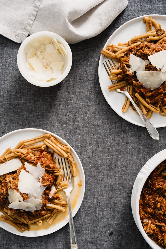 Two plates of italian pulled pork ragu on a grey linen table with a cream cloth napkin and a small bowl of parmesan cheese.