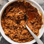 A large white bowl of pulled pork ragu made with leftover pulled pork.