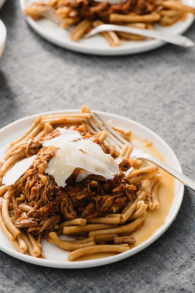 A plate of italian pork ragu made using leftover pulled pork served over whole grain pasta and garnished with parmesan cheese.